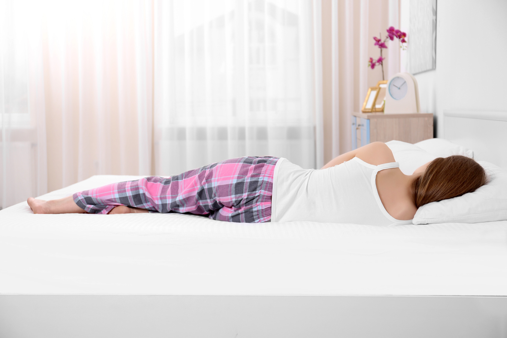 Young woman lying on bed with orthopedic pillow against blurred background. Healthy posture concept